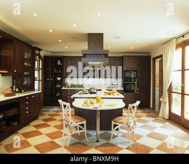 Terracotta+cream checkerboard flooring in large modern Spanish kitchen with dark wood units