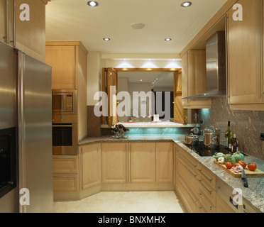 Recessed lighting in modern in modern Spanish kitchen with pale wood fitted units and large American-style fridge - Stock Photo
