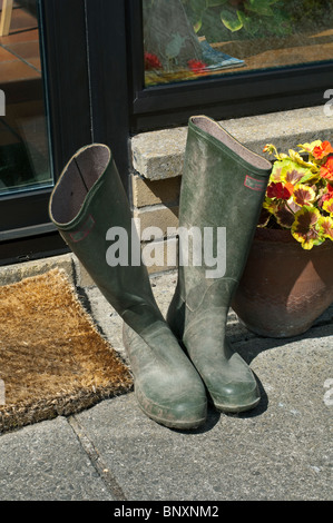 A pair of old used worn green wellington boots outside on the doorstep - Stock Photo