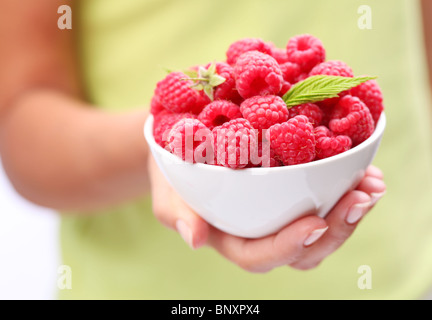 Crockery with raspberries in woman hand. - Stock Photo
