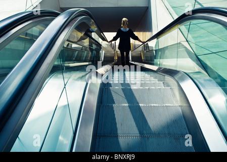 Riding escalator down, rear view - Stock Photo