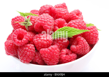 Crockery with beautiful ripe raspberries. Isolated on a white background. - Stock Photo