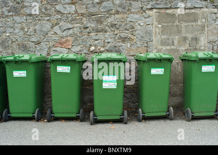 A lin of recycling green wheelie bins against a wall - Stock Photo