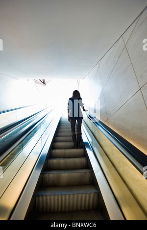 Riding escalator, rear view - Stock Photo