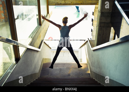 Teenage girl in stairwell, jumping in midair, rear view - Stock Photo