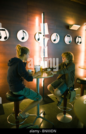 Young friends having coffee together in cafe - Stock Photo