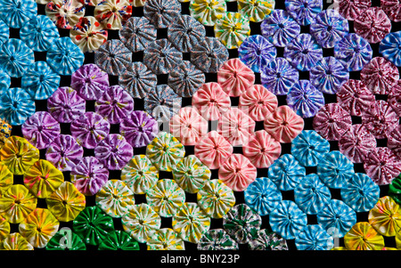Unusual handmade vintage fabric abstract multicolor yo yo quilt of colorful merging squares and circles close up, - Stock Photo
