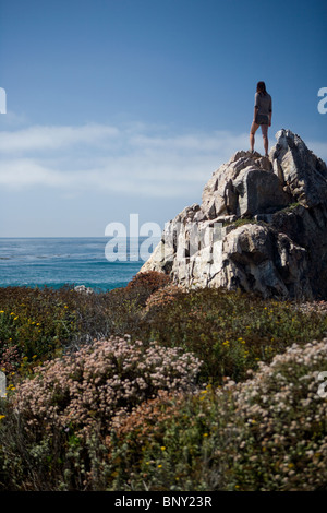 A young woman stands atop a rock overlooking the Pacific Ocean - Stock Photo