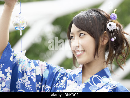 Young woman looking at wind chime - Stock Photo