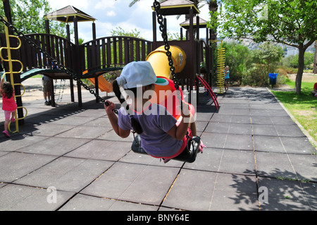 Israel, Haifa, The Kishon Park on the banks of the Kishon river Girl plays in a public playground - model release - Stock Photo