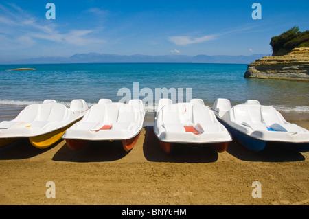 Corfu beach. Tourist boats on beach at Sidari on the Greek island of Corfu Greece GR view to Albanian mountains - Stock Photo