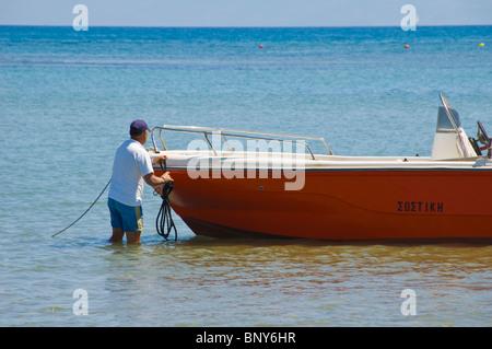Corfu beach. Local boatman tying up his motorboat on beach at Sidari on the Greek island of Corfu Greece GR - Stock Photo