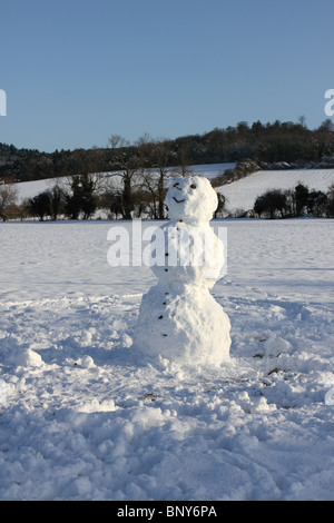Snowman in field with Chiltern Hills behind at Mill End, Hambleden, Buckinghamshire, England, UK - Stock Photo