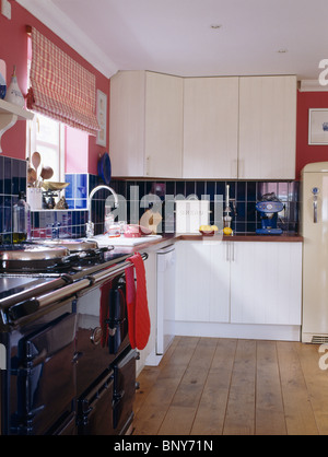 A kitchen with red aga oven in a 1970 39 s style house which for Red fitted kitchen