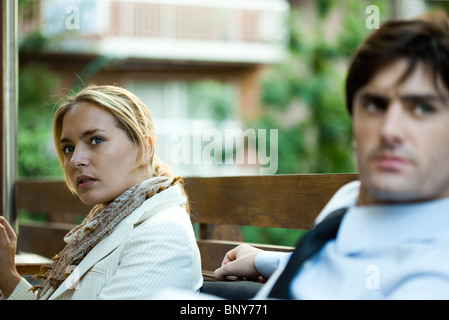Couple sitting outdoors, woman looking away in distraction - Stock Photo