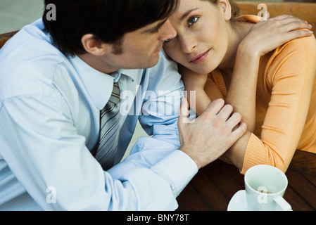 Couple sitting together in cafe, woman resting her head on man's shoulder - Stock Photo