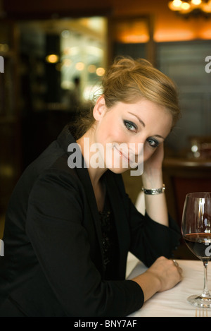 Woman daydreaming in restaurant, portrait - Stock Photo