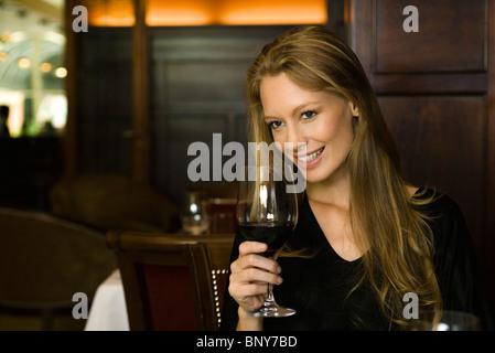 Woman enjoying glass of red wine in restaurant - Stock Photo