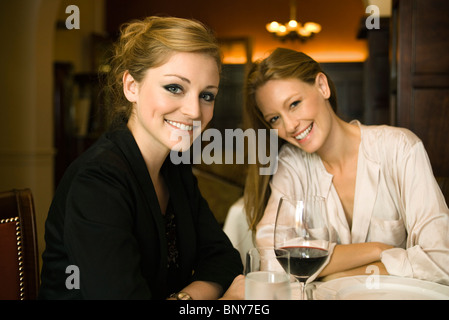 Woman having glass of wine with friend in restaurant - Stock Photo