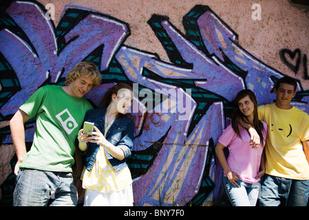 Young friends hanging out together, one holding cell phone - Stock Photo