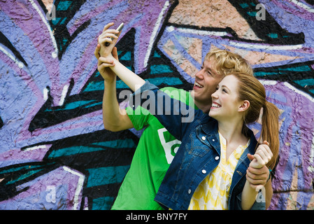 Young couple photographing themselves with cell phone - Stock Photo