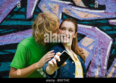Young couple photographing themselves with cell phone, male kissing female's cheek - Stock Photo