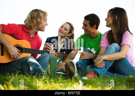 Young man sitting on grass with friends, playing acoustic guitar - Stock Photo