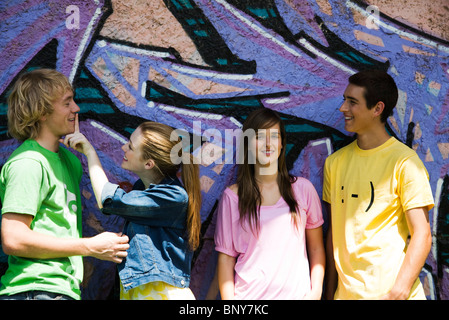 Young friends hanging out in front of graffitied wall - Stock Photo