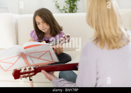 Girl having a lesson on the guitar - Stock Photo