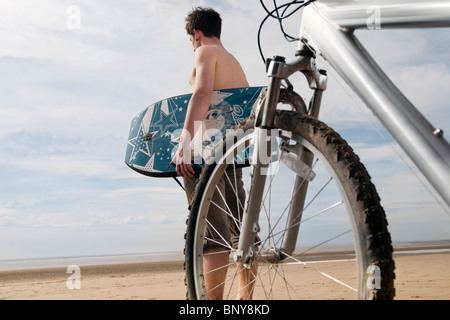Man on beach with bike and boogie board - Stock Photo