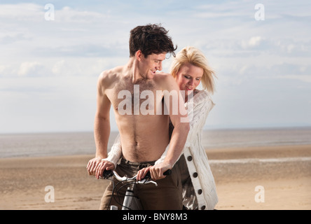 Couple on beach on bike - Stock Photo