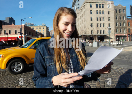 Woman reading a letter in the street - Stock Photo