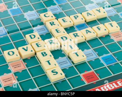Scrabble Board with Debts - Stock Photo
