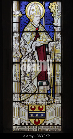 A stained glass window depicting Saint Nicholas of Myra holding three bags of gold and dressed as Bishop of Myra - Stock Photo