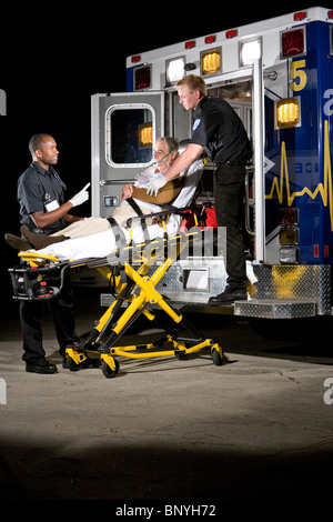 Paramedics caring for elderly patient on stretcher in ambulance at night - Stock Photo