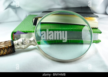 Magnifying glass magnifying two notebooks - Stock Photo