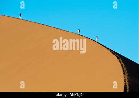 Tourists ascending dune 45 at Sossusvlei in Naukluft Park Central Namib desert Namibia - Stock Photo