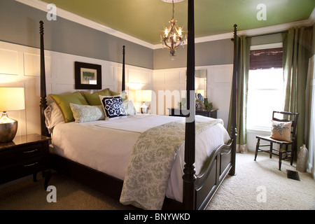 Contemporary bedroom with double four poster. American style with use of matching colors gray, white, acid green - Stock Photo