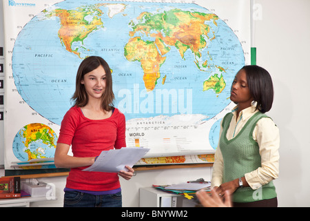 multi ethnic diversity racially diverse multicultural cultural interracial teenage girl reading class gives report - Stock Photo