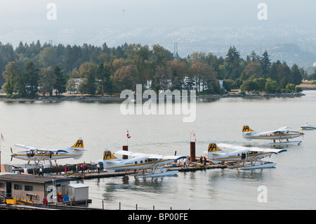 A high angle view of four Harbour Air seaplanes (de Havilland Canada DHC-3T ) in Coal Harbour, Vancouver, Canada. - Stock Photo