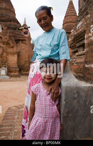 old woman and small girl beside temples at Bagan, Myanmar - Stock Photo