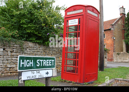A traditional red telephone box on a street in a U.K. village. - Stock Photo