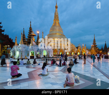 view of Shwedagon Pagoda at dusk with pilgrims, Yangon, Myanmar - Stock Photo