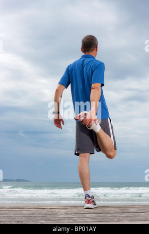 Runner doing stretching exercise on a beach - Stock Photo