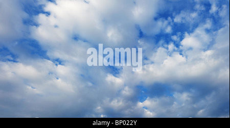 White cumulus clouds in the summer blue sky - Stock Photo