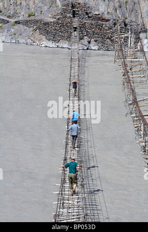 Pakistan - Karakorum - Hunza Valley - tourists crossing a suspension bridge across the Hunza River - Stock Photo