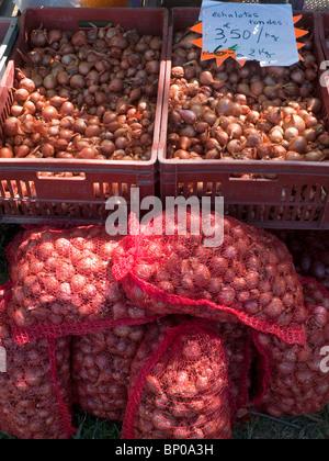 Market stall with sacks of shallots - France. - Stock Photo