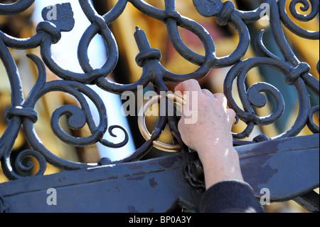 Tourist rubbing the brass ring on The Beautiful Fountain or Schoner Brunnen in Nuremberg Germany Nurnberg Deutschland - Stock Photo