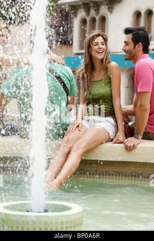 Young woman cooling her feet in fountain - Stock Photo