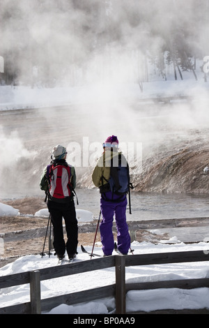 Two Skiers looking out over a geyser in Yellowstone national Park,Wyoming,USA - Stock Photo